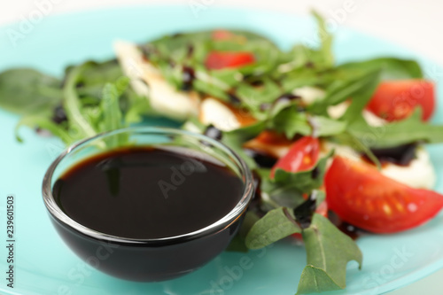 Bowl of balsamic vinegar on plate with vegetable salad, closeup