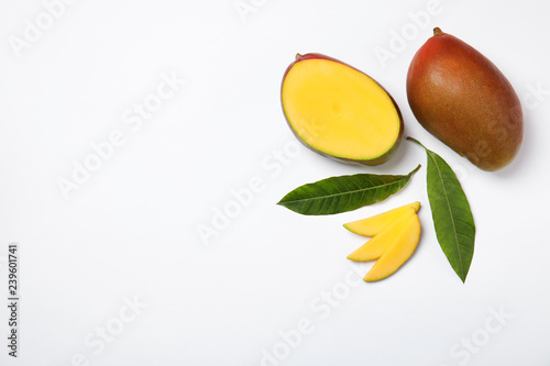 Tropical cut and whole mango with green leaves isolated on white, flat lay. Space for text