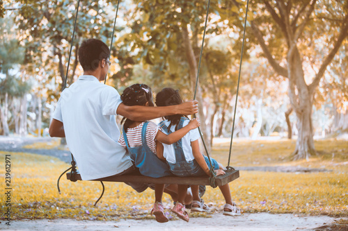 Foto  Asian father and daughter having fun to ride on swings together in playground at