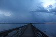 Looking down the wooden fishing pier jetty at sunset with thick blue gray storm clouds