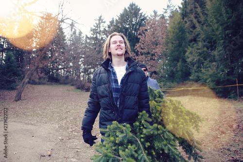 Fotografie, Obraz  Handsome guy carrying a cut Christmas fir at a Christmas tree farm