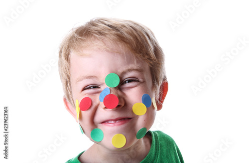 Foto Smiling mischievous boy with round stickers on his face