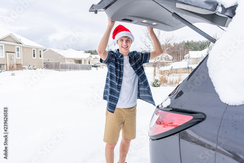 In de dag Illustratie Parijs Excited young traveler loading up his car for his winter vacation. He is dressed in summer clothing and a Santa hat while standing in the snow.
