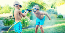 Two Brothers Play On A Summer Hot Day In The Garden. Children Are Splashing With A Garden Hose.