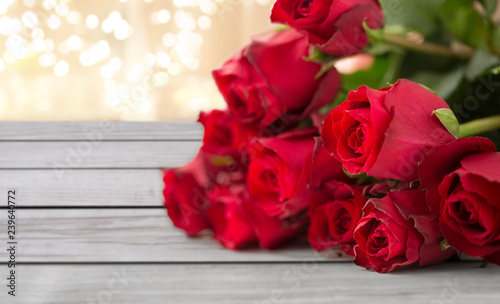 Valokuva flowers, valentines day and holidays concept - close up of red roses bunch on wo