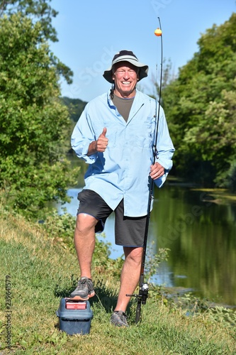 Fotografie, Obraz  Older Retiree Adult Male Fisherman With Thumbs Up With Rod And Reel Outdoors