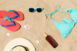 vacation, travel and summer holidays concept - straw hat, flip flops, sunglasses and sunscreen oil with seashells on beach sand