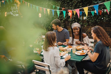 Friends Having Food At Table During  Party In Backyard