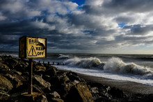Danger Keep Off Rocks Sign During Storm With Waves
