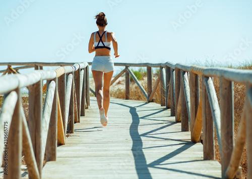 Fototapeta active sports woman in sport clothes on ocean coast jogging obraz na płótnie