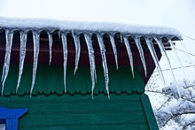 A Row Of Icicles On The Roof Under The Snow Against A Green Wooden Wall