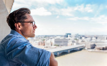 UK, London, Man Looking At The City On A Roof Terrace