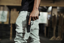 Close-up Of Man Holding A Pistol In An Indoor Shooting Range