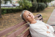 Portrait Of Senior Woman Relaxing On Bench