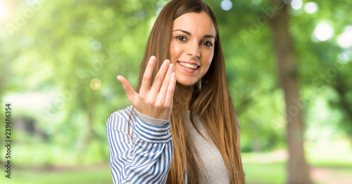 Fotografiet  Young girl with striped shirt inviting to come with hand