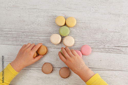 Girl playing with colorful French macarons on white wooden table