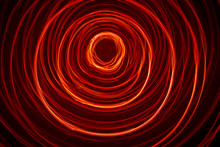 A Beautiful, Bright Light Swirl Of Red Color. Futuristic Light Painting On A Black Background. Round Light Circles