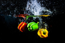 Fresh Colourful Bell Pepper Splashing In Water On Black Background.