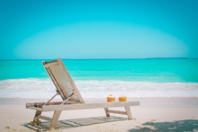Two Coconut Drinks And Chair On Tropical Beach