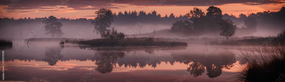 Fototapety, obrazy: Panorama with trees and small island reflecting in the water in the red morning light just before sunrise above nature reserve Hatertse Vennen, Nijmegen, The Netherlands