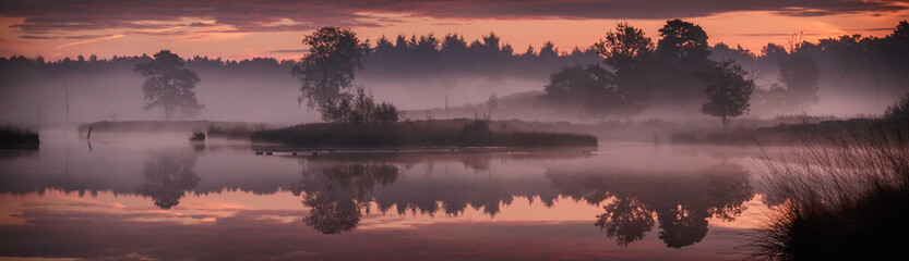 Panorama with trees and small island reflecting in the water in the red morning light just before sunrise above nature reserve Hatertse Vennen, Nijmegen, The Netherlands