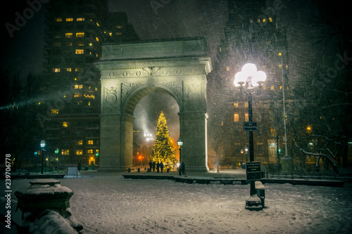 Deurstickers New York Winter holiday night view of the Washington Square Park with a Christmas Tree under falling snow in New York City