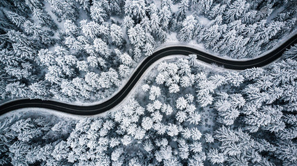 Curvy windy road in snow covered forest, top down aerial view