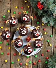 Homemade Funny Cupcakes Santa's Reindeers On A Wooden Background. Christmas Idea For Kids.