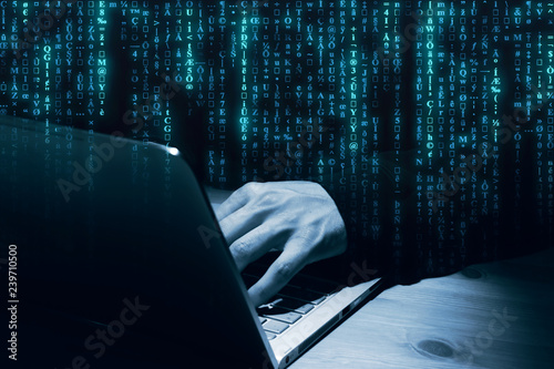 Mann beim Hacken am Notebook