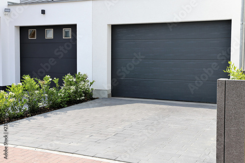 Obraz Zwei moderne neue Garagentore (Sektionaltore) in einem Wohngebiet - fototapety do salonu