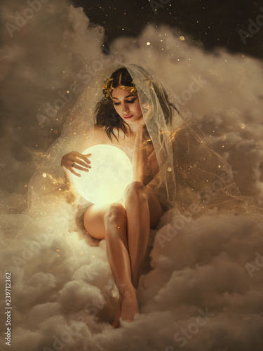 Fotografia gorgeous slender sexy lady sits in the clouds and holds the moon in her hands