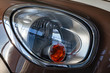 The front stylish shining headlight of white and red color is equipped on the body with a designer inscription inside the mini as a sign of the brown brand car model Cooper.