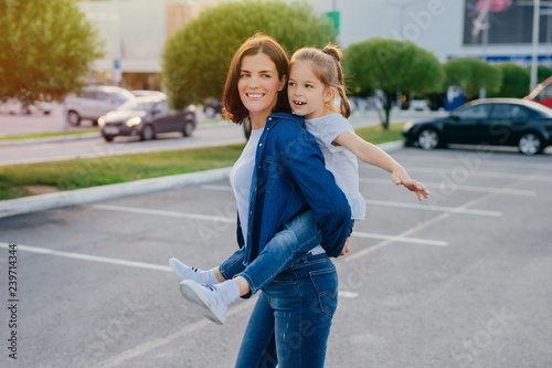 Image of affectionate mother gives piggyback to small daughter, smile broadly, have outdoor walk, pose against blurred background with cars, play together Wallpaper Mural