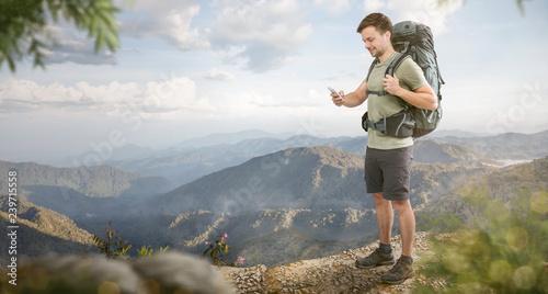 Wanderer vor weiter Landschaft schaut aufs Smartphone