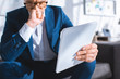selective focus of digital tablet in hand of worried businessman