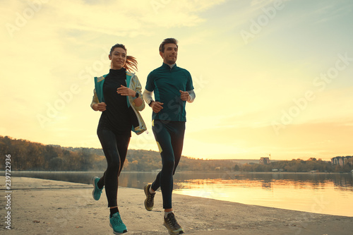 Fotografie, Obraz  Young man and woman out for a run on the lake at the sunrise