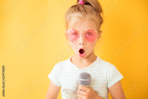 Fotografía  Happy little girl singing into a microphone the song on yellow background