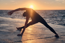 Anonymous Female Doing Yoga During Sunset Near Sea