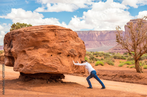 Girl pushing big stone hard, impossible and useless concept Canvas Print