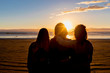 Three Friends Silhouetted at the Beach at Sunset