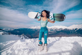 Girl snowboarder stands with snowboard on mountains top