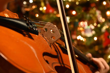 A Young Person Playing The Violin With A Chrismas Tree In The Background