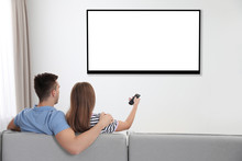Couple Watching TV On Sofa At Home. Mockup For Design