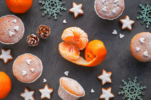 Top View Of The Table With Satsumas, Sugar-sprinkled Muffins And Christmas Star Cookies On Dark