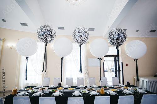 Obraz Festive dinner table decor. White and black balloons hang over the restaurant table served with delicious food - fototapety do salonu