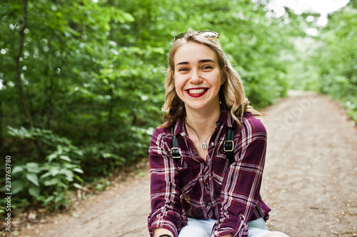 Fotografía  Portrait of a beautiful blond girl in tartan shirt sitting on the ground in the countryside