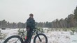 Professional extreme sportsman biker stand a fat bike in outdoors. Cyclist recline in the winter snow forest. Man walk with mountain bicycle with big tire in helmet and glasses. Slow motion in 180fps.