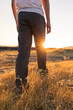 Man walking through grassy field at golden our with sun peaking behind leg