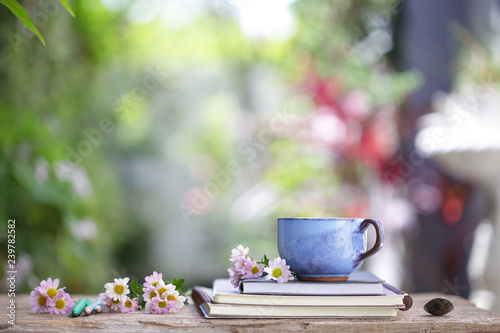 Photo Stands Cafe Old blue cup and notebook with flower on wooden table