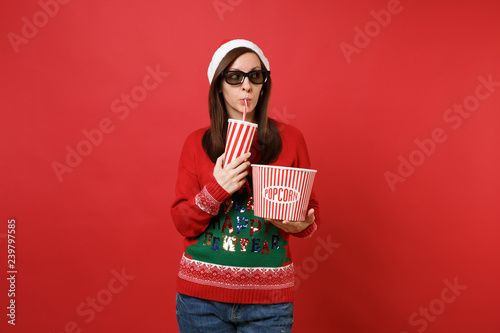Photo Curious Santa girl in 3d imax glasses watching movie film, hold popcorn cup of soda looking aside isolated on red background